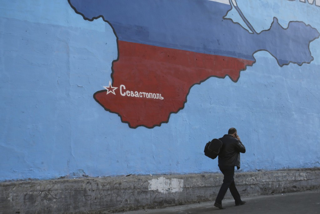 A man passes a mural showing a map of Crimea in Russian national colours on a street in Moscow